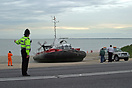 Traffic is stopped along the coastal road to allow the hovercraft to b...